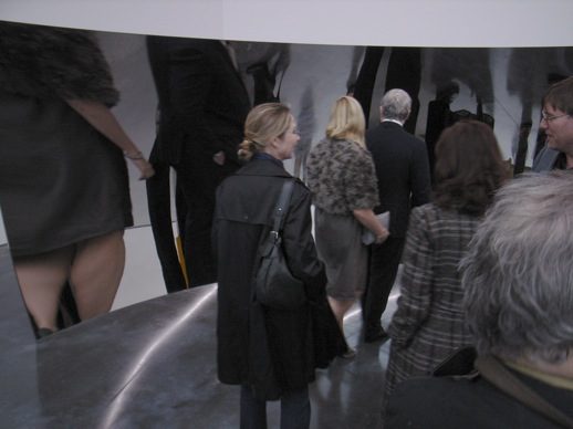 Guests walking around the giant distorting mirror sculptures.