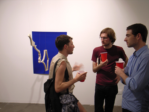 A few guests to the gallery chatting in front of a very intensely colored canvas.