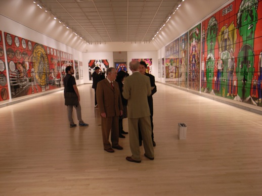 Gilbert and George in the main fifth floor gallery filled with their massive works on a grid, resembling stained glass windows.