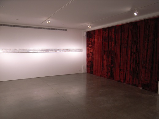 The space is divided by a big red curtain. What is behind the curtain?