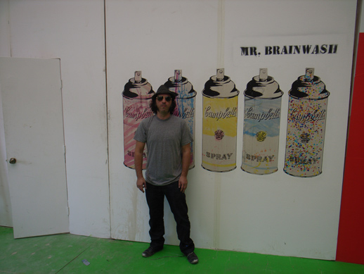 Mr. Brainwash in front of his work.