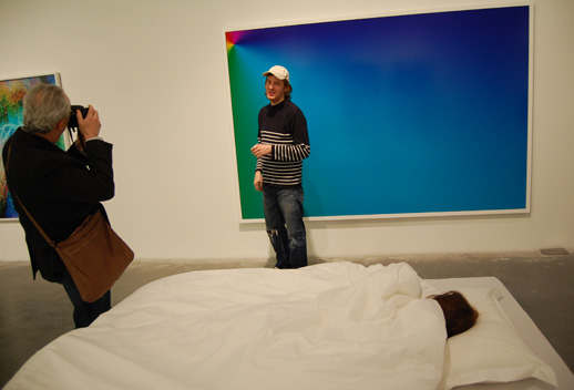 Cory Arcangel posing in front of his Photoshop print while someone sleeps.