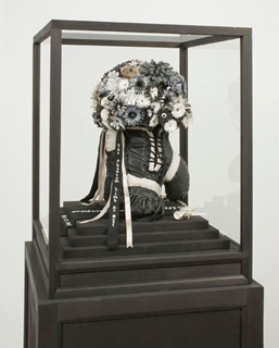 Dario Robleto, ''Sinew of Purpose'' 2008. Leather, cut paper, lead and silver coated roses, ribbon, waxed thread, sepia and ink stained willow, glass. 60 x 22 x 22 in. Courtesy Lisa Cooley.