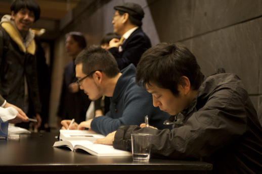Taisuke Koyama and Kohei Nawa signing the books.