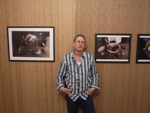 Photographer and brain researcher, Dr. Eran Gilat in front of his photographs.